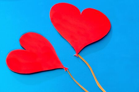 Two red paper hearts on blue background - stock photo