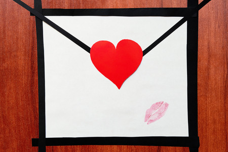 Hand made envelope with heart and lipstick kiss on the wooden table - stock photo
