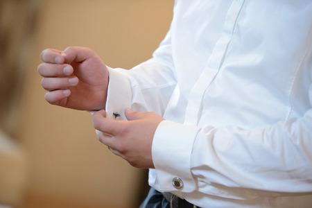 cufflink: Wedding preparation. Groom is putting on the cufflink.