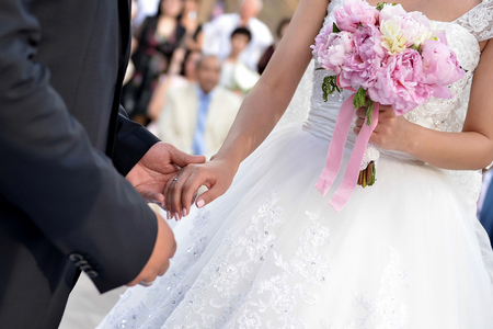 Hands holding on wedding. The bride holds flowers Standard-Bild