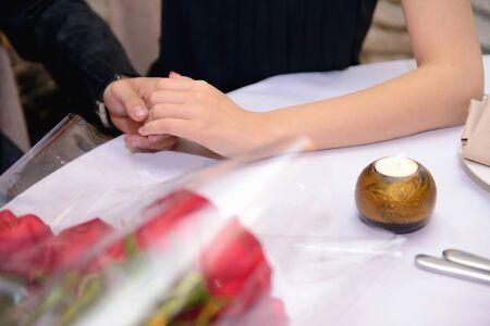 Engagement. Hands holding in the restaurant Standard-Bild