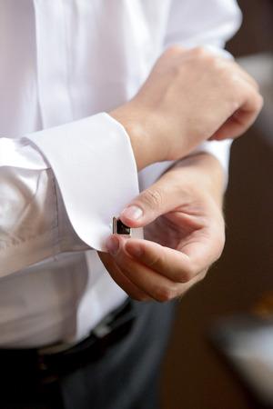 Wedding preparation. Groom is putting on the cufflink.