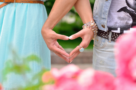 Two hands holding a heart symbol. Picture made outdoors throught the flowers