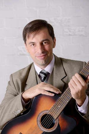 Artist sitting portrait , holding acoustic guitar