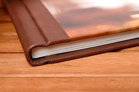 Big photobook lay on wooden table close up. Hard leazard cover Standard-Bild