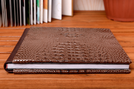 Photobook lay on wooden table with hard fake leather cover Standard-Bild
