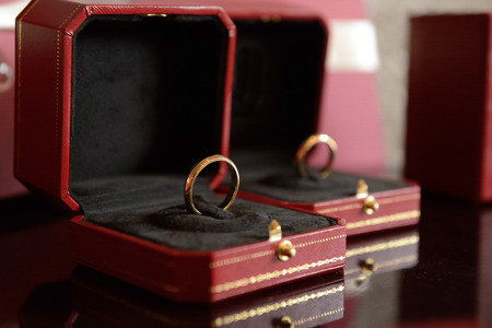 Bride and groom wedding rings in luxury red boxes