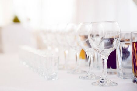 Glasses for vine and vodkz on the white surface with soft warm photo filter
