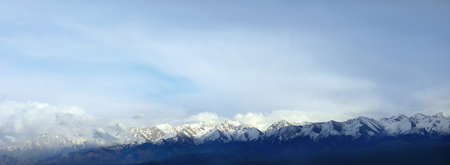 the peaks of the mountains through the haze panorama