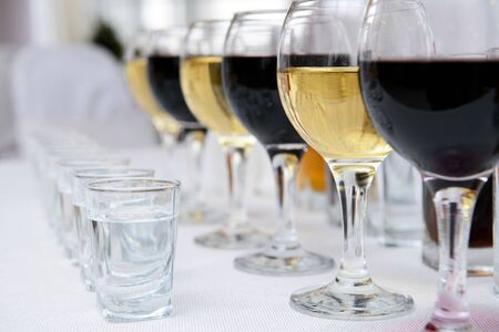 Glasses of red and white vine in restaurant standing on the white surface
