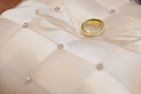 Bride and groom wedding rings lay on white pillow