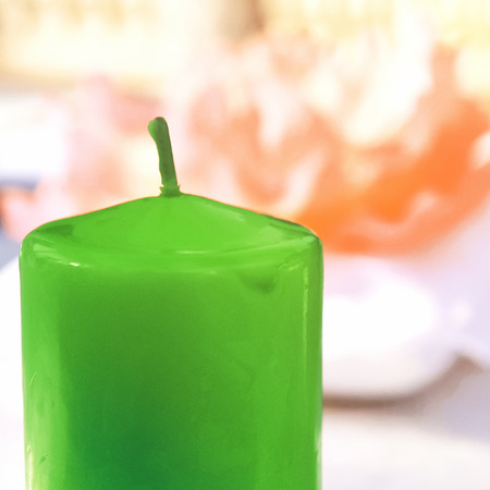 Big green candle on the table, orange blured background Standard-Bild