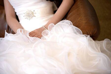 Bride hands lay on wedding dress