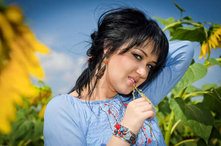 Beautiful white girl with deep black hair in a field with sunflowers in a blue folk shirt Standard-Bild - 161513069