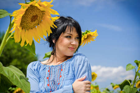 Beautiful white girl with deep black hair in a field with sunflowers in a blue folk shirt Standard-Bild
