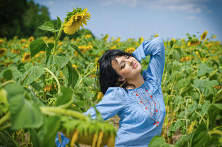 Beautiful white girl with deep black hair in a field with sunflowers in a blue folk shirt Standard-Bild - 161513072