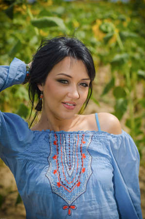 Beautiful white girl with deep black hair in a field with sunflowers in a blue folk shirt Standard-Bild - 161513073