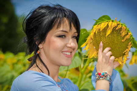 Beautiful white girl with deep black hair in a field with sunflowers in a blue folk shirt Standard-Bild - 161513076