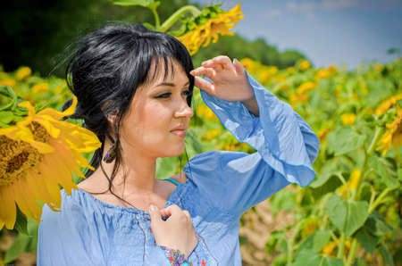 Beautiful white girl with deep black hair in a field with sunflowers in a blue folk shirt Standard-Bild - 161513078