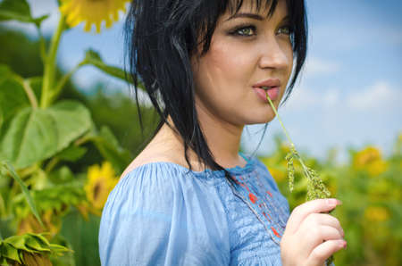 Beautiful white girl with deep black hair in a field with sunflowers in a blue folk shirt Standard-Bild - 161513079