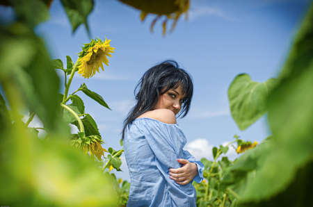 Beautiful white girl with deep black hair in a field with sunflowers in a blue folk shirt Standard-Bild - 161513080