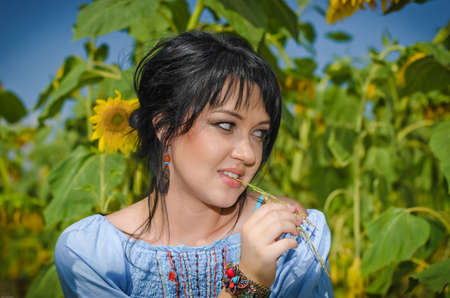 Beautiful white girl with deep black hair in a field with sunflowers in a blue folk shirt Standard-Bild - 161513083