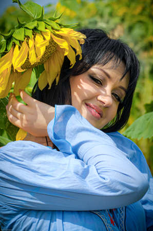 Beautiful white girl with deep black hair in a field with sunflowers in a blue folk shirt Standard-Bild - 161513084