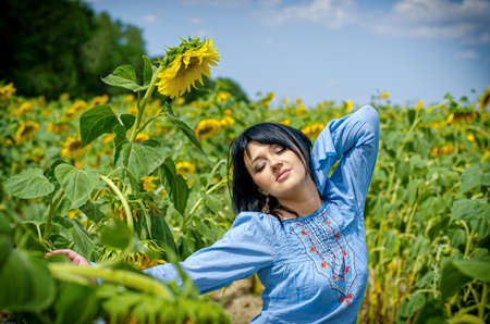 Beautiful white girl with deep black hair in a field with sunflowers in a blue folk shirt Standard-Bild - 161513088