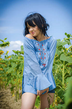 Beautiful white girl with deep black hair in a field with sunflowers in a blue folk shirt Standard-Bild - 161513090