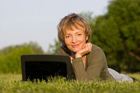 Woman with notebook lying on the grass in park