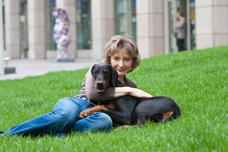 The young woman with a doberman dog on a grass Banco de Imagens