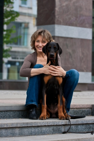 The young woman embrace a doberman dog on a ladder in the city