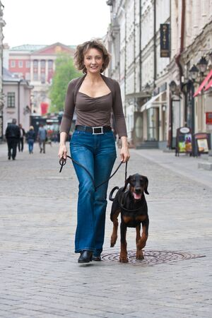 The woman walks with a dog on city street Banque d'images