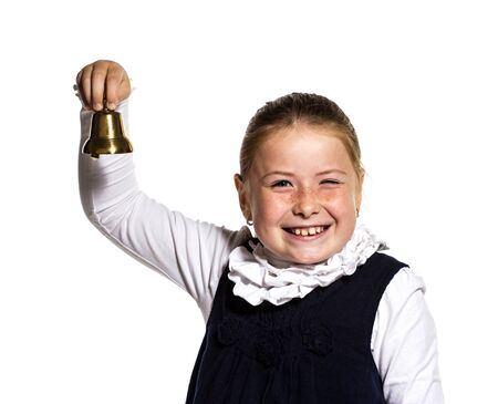 Winking Young school girl ringing a golden bell on white background
