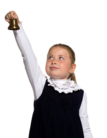 Young school girl ringing a golden bell on an outstretched arm on white background photo