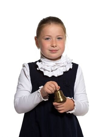 Young school girl ringing a golden bell on white background