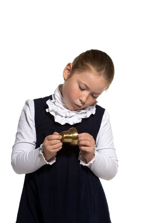 Young school girl looking to golden bell on white background photo