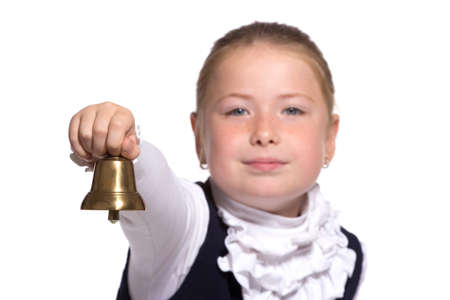 Young school girl ringing a golden bell on white background focused on bell photo