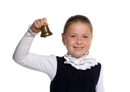 Young school girl ringing a golden bell on white background photo