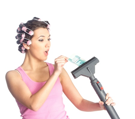 Funny girl with hair curlers on her head pull banknote from vacuum cleaner isolated on white. photo