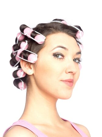 Funny girl with hair curlers on her head isolated on white photo