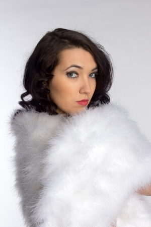 Beautiful girl in a fur shawl on gray background photo