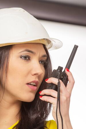 radio active: Serious female construction worker talking with a walkie talkie