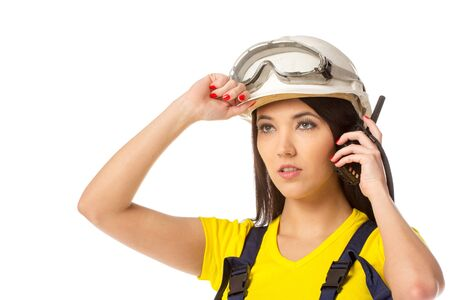 Serious female construction worker talking with a walkie talkie photo