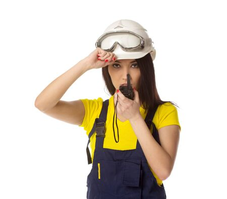 radio active: Serious female construction worker talking with a walkie talkie, isolated on white Stock Photo