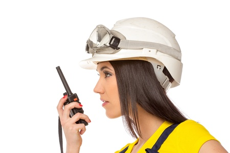 walkie: Serious female construction worker talking with a walkie talkie