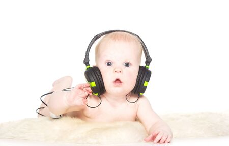 Portrait of 6 month old boy with headphones, isolated on white photo