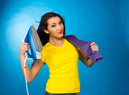 Houseworks, woman hold an iron in hand, on blue background photo