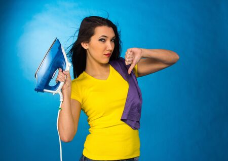 Houseworks, woman hold an iron in hand, and hand thumb down, on blue background photo