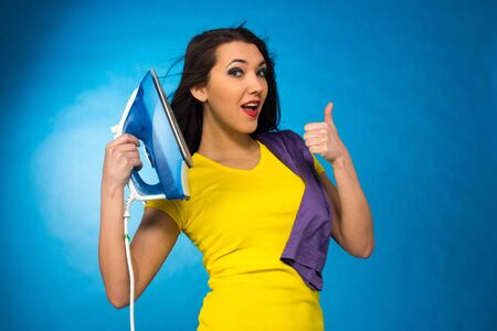 Houseworks, woman hold an iron in hand, and hand thumb up, on blue background photo